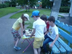 Дети играют в шашки на свежем воздухе